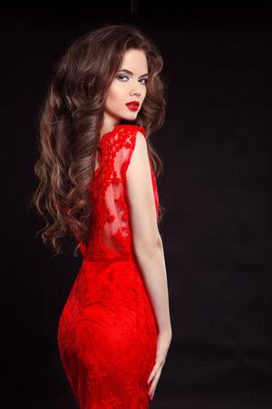 Piękna seksowna kobieta w czerwonej sukni mody samodzielnie na czarnym tle. Makijaż. Beauty Brunette Girl. Zdrowe długie włosy.
