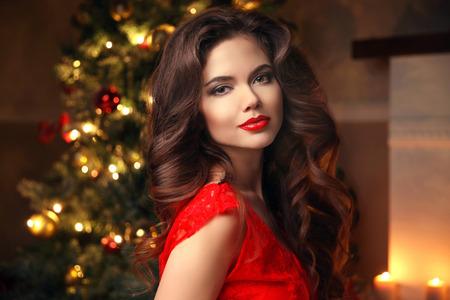 クリスマス サンタ。美しい笑顔の女性モデル。メイク。健康的な長い髪のスタイル。クリスマス ツリーのライトの背景に赤いドレスのエレガントな
