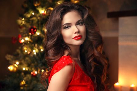 Christmas Santa. Beautiful smiling woman model. Makeup. Healthy long hair style. Elegant lady in red dress over christmas tree lights background. happy new year.