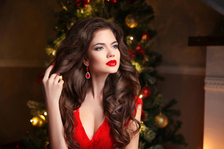 Long hair. Makeup. Christmas Woman. Beautiful girl portrait. Elegant lady in red dress with wavy healthy hairstyle over christmas tree x-mas background. Happy new year.