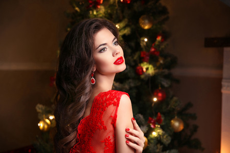 female christmas: Beautiful smiling Woman near Christmas tree. Brunette girl with red lips makeup, long wavy hair style, manicured nails. Fashion earrings jewelry. Attractive lady posing in room. Stock Photo