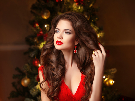 Christmas Woman. Long hair. Fashion earrings. Makeup. Beautiful girl portrait. Elegant lady in red dress with wavy healthy hairstyle over christmas tree x-mas background. Happy new year.