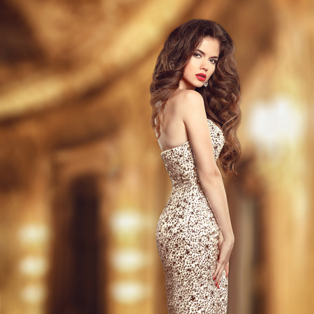 woman dress: Glamour style beauty portrait. Beautiful young woman in elegant dress in golden modern stylish interior. Stock Photo