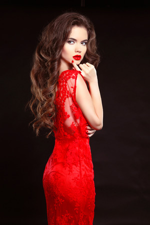 Beauty fashion elegant woman in red dress isolated on black background. Makeup. Long wavy hair style. Nailpolish.