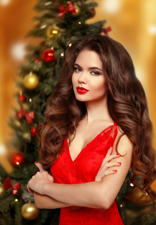 Christmas woman. Beautiful smiling girl model. Makeup. Healthy long hair style. Manicured nails. Elegant lady in red dress over christmas tree lights background. Stock Photo