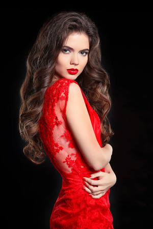 Long hair. Beautiful brunette woman in red lace dress. Beauty girl model with sensual lips makeup and healthy curly hairstyle posing isolated on black studio background. Stock Photo