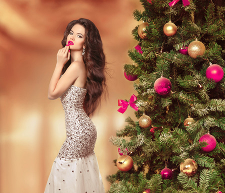 Long Hair. Beautiful Brunette Girl in fashion luxury dress style. Healthy wavy Hairstyle. Beauty Model Woman near christmas tree celebration New Year. Stock Photo