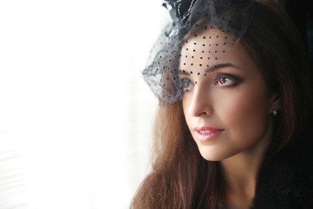 Retro portrait of Elegant brunette woman wearing in hat with veil looking out window. Stock Photo