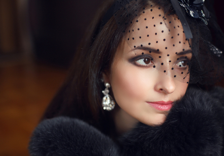 Elegant brunette retro woman wearing little hat with veil and luxury fur coat. Diamond earrings. Makeup.