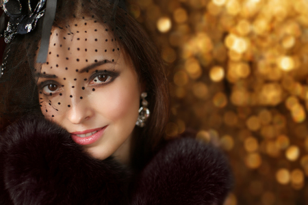 Beautiful fashion retro smiling woman wearing in hat with veil and luxury fur coat over Christmas holiday bokeh background, elegant female portrait.