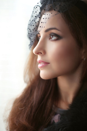 Elegant brunette woman in hat with veil looking out window, profile face, perfect skin facial make-up. Stock Photo