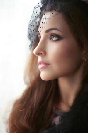 perfil de mujer rostro: mujer morena elegante en sombrero con velo mirando por la ventana, la cara de perfil, la piel perfecta maquillaje facial. Foto de archivo