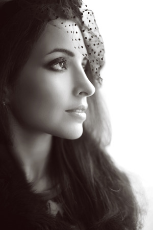 Retro portrasit of  Elegant brunette woman in hat with veil looking out window, profile face, perfect skin facial make-up.