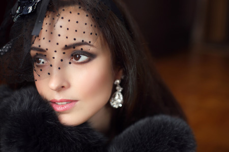 Beauty fashion retro woman wearing little hat with veil and luxury fur coat, elegant female portrait. Makeup. Jewelry. Stock Photo