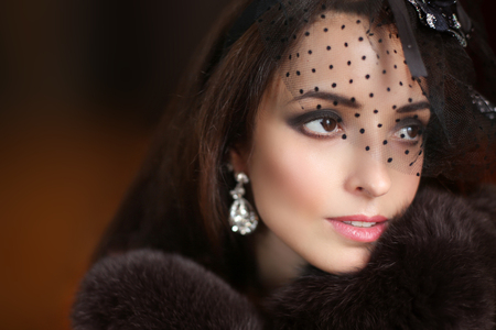 Beauty retro woman portrait in hat with lace. Elegant lady in  luxury fur coat and fashion earrings. Winter.