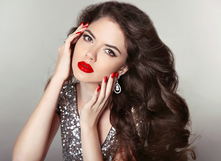 Long hair. Makeup. Beautiful girl portrait. Brunette fashion woman with red lips, manicured nails, healthy curly shiny hairstyle posing on studio background. Stock Photo