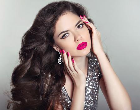 unas largas: Maquillaje. Retrato hermoso de la chica. Pelo largo. moda mujer morena con labios rojos, u�as cuidadas, sana peinado rizado brillante que presenta en fondo del estudio.