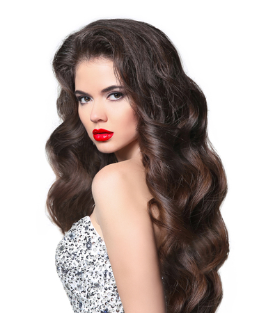 Wavy hair. Beautiful bride brunette young woman model with healthy long brown hairstyle and red lips makeup. Elegant lady in luxury beaded and sequins wedding dress.