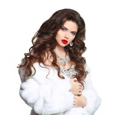 뷰티 메이크업입니다. 긴 머리. 흰색 럭셔리 밍크 모피 코트에서 아름 다운 여자. 패션 보석 액세서리. 우아한 레이디 흰색 배경에 고립.