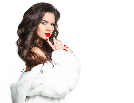 Hermosa joven con corte de pelo largo pelo rizado y labios rojos de maquillaje, moda mujer en abrigo de pieles aislado en el fondo blanco. Foto de archivo