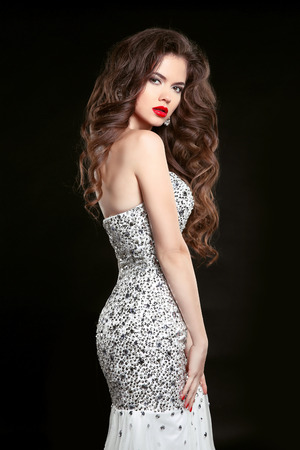 Beautiful elegant woman in fashion dress isolated on black background. Makeup. Beauty Brunette Girl. Healthy Long Hair.