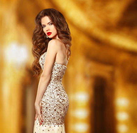 Beauty fashion elegant woman model in luxury dress with beaded and sequin. Attractive sensual girl posing in golden modern stylish interior.