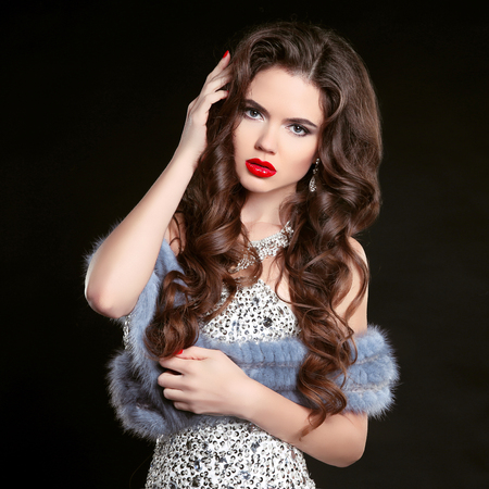 Beauty fashion portrait of young beautiful brunette girl in luxury dress with blue mink fur coat, woman with long healthy wavy hair.