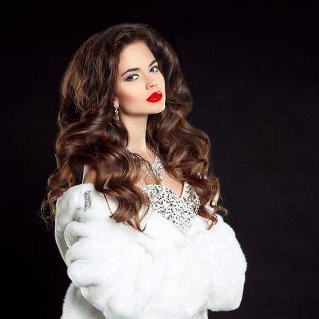 Beauty portrait of beautiful elegant woman with red lips makeup and long wavy hair style, wearing in luxury dress and white fur coat isolated on black studio background. Stock Photo