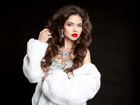 Beauty Makeup. Long hair. Beautiful Woman in Luxury white mink Fur Coat. Fashion jewelry accessories. Elegant lady isolated on black background.