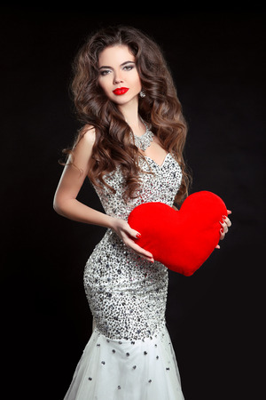 bride dress: Beautiful sexy brunette Woman present red heart, Valentines day. Elegant girl model with long wavy hair style, makeup. Lady in luxury dress isolated on black background.