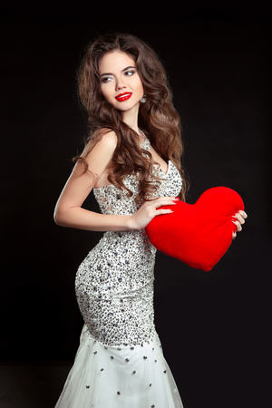 Beautiful smiling girl with red heart in luxury dress isolated on black background. Elegant brunette woman model with long wavy hair style, makeup. Stock Photo