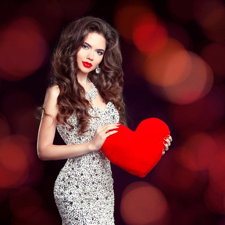 Beautiful brunette girl with red heart gift for Valentines Day. Elegant slim woman in luxury dress isolated on holiday dark lights background.