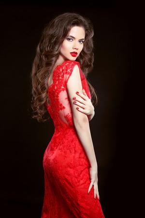 Mujer atractiva hermosa en vestido de la manera rojo sobre fondo negro. Maquillaje. Belleza morena chica. Pelo largo sano. uñas cuidadas.