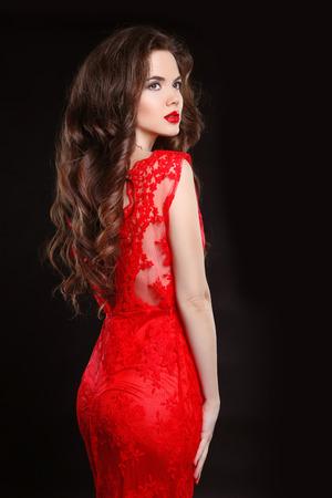 Hermosa mujer elegante de moda en el vestido rojo aislado sobre fondo negro. Maquillaje. estilo de pelo largo y ondulado.