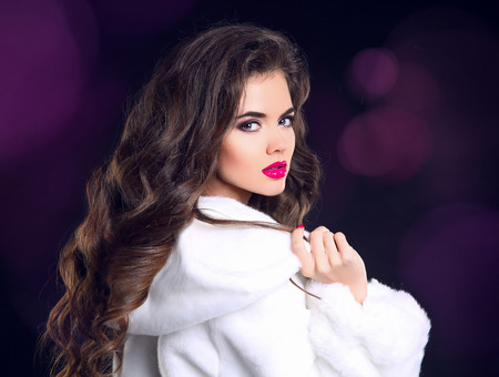 Winter beauty woman in white fur coat. Fashion model portrait. Healthy long wavy hairstyle. Elegant female.