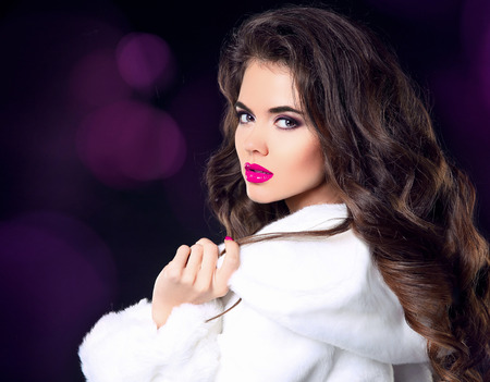 Fashion woman in white fur coat, beauty lady model portrait. Sensual lips makeup, long wavy hair style. Brunette girl model isolated on dark background.