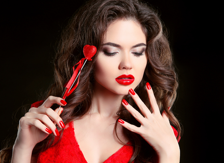 Red lips, manicured nails. Beautiful young woman model with beauty makeup, curly hairstyle, polish manicure. Brunette girl with heart isolated on black background, Valentine day.