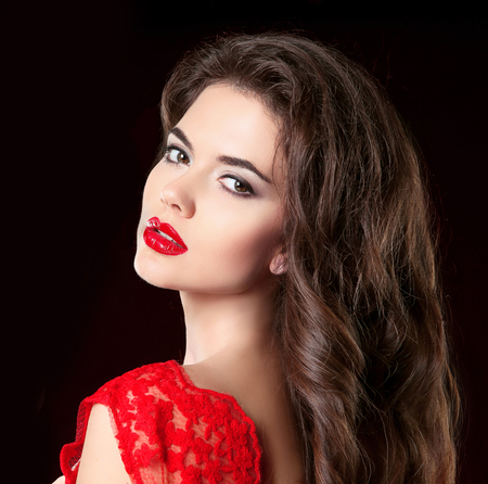 Beauty Portrait of beautiful brunette woman with red lips and curly hairs in dress isolated on black background.