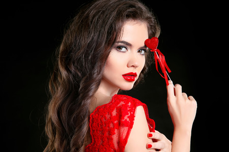 Red lips. Beautiful brunette girl with heart gift for Valentines Day. Sensual woman with long hair style isolated on black background.