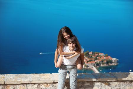 ragazza innamorata: Coppia felice in amore le vacanze estive. Giovane che trasporta sulle spalle la sua bella fidanzata sul mare, mentre fotocamera a ridere. Isola di Sveti Stefan a Budva, Montenegro