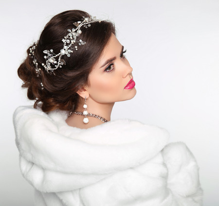 Beauty Fashion Model Girl in white Mink Fur Coat. Wedding hairstyle. Beautiful Luxury Winter Woman isolated on white background. Stock Photo