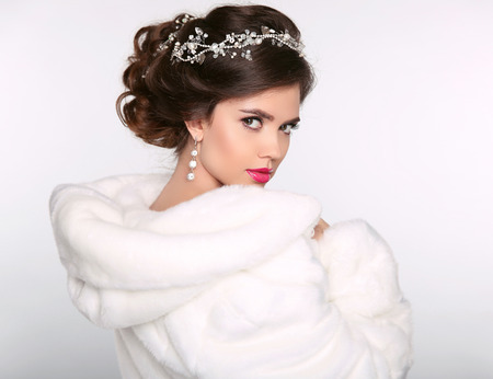 Winter beauty woman in white fur coat. Fashion model portrait. Jewelry. Wedding hairstyle. Elegant female.