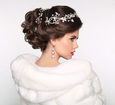 Elegant brunette woman in white fur coat. Wedding Hairstyle. Beautiful fashion bride girl model portrait. Luxury jewelry. Attractive young woman with brown hair.
