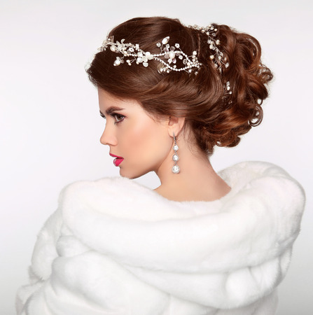Wedding Hairstyle. Attractive girl in white fur coat. Jewelry Earring. Expressive eyes stare. Elegant lady isolated on studio white background. Luxury style.