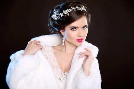 Winter beauty woman in white fur coat. Fashion model portrait. Jewelry. Elegant hairstyle. Elegant female isolated on black background.