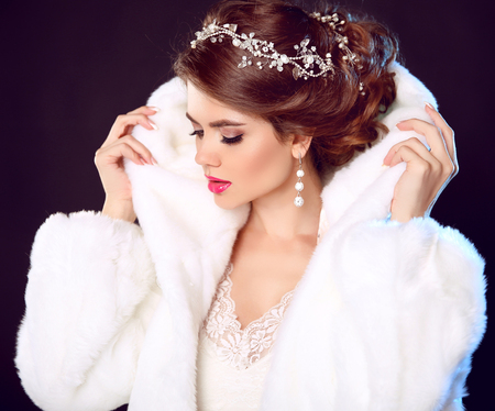 Beauty Fashion Model Girl in white Mink Fur Coat. Wedding hairstyle. Makeup. Beautiful Luxury Winter Woman isolated on dark background.