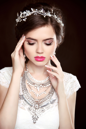 Luxury jewelry. Elegant woman. Beautyfashion portrait of brunette girl model with makeup, diamond jewellery,isolated on black background. Stock Photo
