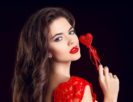 Beauty Makeup. Beuatiful girl with red lips and Valentine heart isolated on black background.