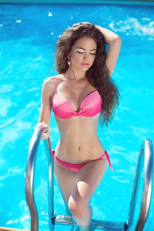 junge nackte m�dchen: Bikini-Modell. Sch�ne sexy M�dchen im blauen Pool am Strand posiert. Ferien. Gebr�unte Frau.