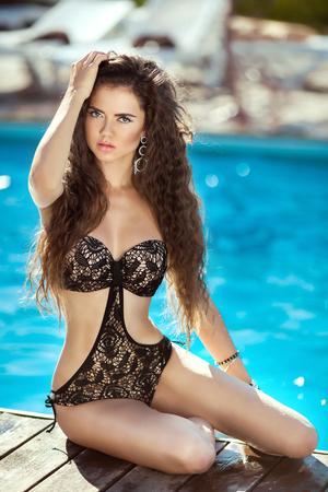 Bikini model. Beautiful brunette girl model with long wavy hair, sunburn by blue water swimming pool on the beach. Vacation. Tanned woman.